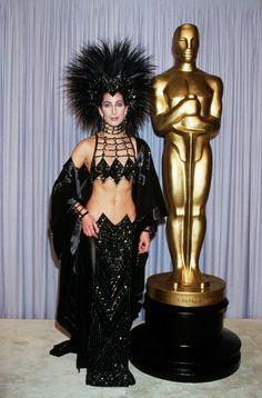Самые обсуждаемые наряды знаменитостей ШЕР В 1986 году певица и актриса появилась на церемонии вручения премии Академии кинематографических искусств и наук в черном платье Bob Mackie с головным убором из перьев.