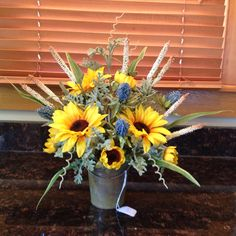 Sunflowers, sea holly and grasses in a weathered bucket silk flower design arrangement.