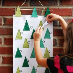 Create a cute and crafty holiday treat for your little ones with this felt tree scape Advent calendar!