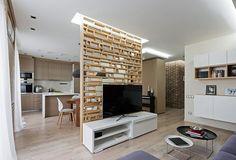 Apartamento decorado com madeira,a divisória permite a interação entre o living e a cozinha,sem deixar de ser uma decoração.