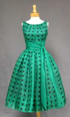 1950's dress in green organdy with black polka dots. Sleeveless bodice with gathered solid organdy waist and sash (can be tied in to a bow if you like). Dress has a full skirt  Rear metal ziper. Lined in acetate