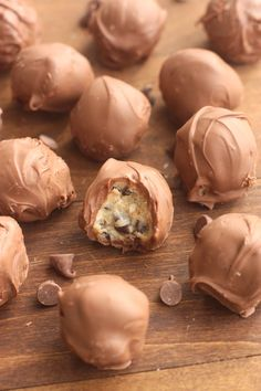 A dozen Chocolate Chip Cookie Dough Truffles on a wooden table, with one bite taken out of one of the truffles.
