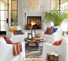 Living Room decor ideas - cozy seating area at fireplace with white slipcovered chairs, pops of blue and red.  Amelia Chandelier from Pottery Barn.