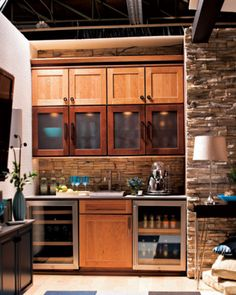 A combination butler's pantry and bar is positioned to the right of the TV. The decor abounds in textural variety: Recessed-panel cherry cabinetry finished in Crystal (upper and base units) and Mocha (with frosted glass) is set against a backsplash covered with faux stone; more variety is added by the raised-pattern paintable white wallpaper.