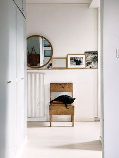 shelf with round mirror resting on top and squarish things next to chair under or a bench perhaps
