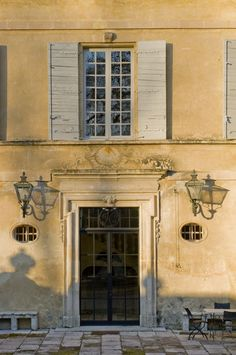 French pastel blue shutters. Warm sandy stone facade. Carved casing at the door. Paned glass doors with dark frames. Metal lanters flanking the door. Notice the scale - look at the table and chairs - this is a grande lady!  - Saint remy de Provence, Luberon