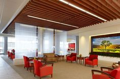 """The lobby is the hospital """"family room,"""" centrally located to connect the entry vestibule, reception, waiting, public elevators, gift shop, dining, and outdoor patio. Decorative glass panels visually separate two seating areas and allow natural light to fill the space. Photo: © Craig Dugan Photography - 2013."""