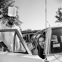 A man in a chef's hat standing behind a station wagon's open door with a young lady seated with a snarl at the camera. Interesting two different races seeming very comfortable with each other while the girl does not seem happy with the photographer. See a Stunning New Set of Vivian Maier Photos from Eye to Eye | Chicago magazine | July 2014