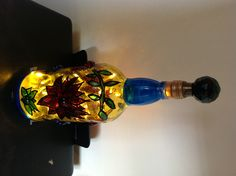 Empty vodka bottle with painted flowers and fairy lights inserted.Finished off with a glass knob attached to a cork.