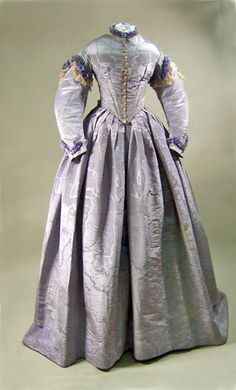 Wedding dress, European, 1865. Lavender corded watered silk trimmed with cream lace. Bodice lined with white glazed cotton.  High round neck edged with band of closely pleated silk with lace inside. Two sloping boned darts each side front from bust to waist. Side seams and button backs also boned. Padded from shoulder to bust. Separate skirt with blue silk waistband. Watch pocket. Manchester Art Galleries