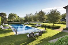 Outdoor furniture by Hervé Baume surrounds the pool.