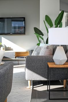 Modern contemporary open plan kitchen living dining room grey walls grey floor tiles grey sofa concrete lamp round coffee table Scandinavian styling