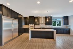 This modern kitchen features black painted shaker cabinets, white quartz with quarz end panels and a gray subway tile backsplash.