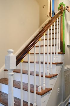 Young House Love | Stairs and Stripes | http://www.younghouselove.com. I like this idea for our stairs. Get rid of the wall and add dowels, opens the space up. Would love to get rid of the carpet and do hard wood stairs with carpet instead.