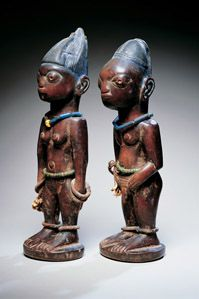 "YorubaTwin Figures (ère ìbejì) C 19 Wood, pigment, beads, and cowrie shells 13 3/4""  -  When a twin dies, a figure is carved to localize the spirit of the deceased. If neglected, its spirit might feel abandoned and invite the soul of the surviving twin to join it in the beyond. The smooth, worn surfaces of these figures show that they have been cared for devotedly. Their elaborate ceremonial coiffures are rubbed with a powdered dye called Rickett's blueing, which was used by the British..."