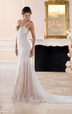 This Old Hollywood glamour wedding dress with long train from Stella York features sheer lace cut-outs for a very sexy silhouette. Lace and tulle over matte-side lustre satin sparkles with crystal beading for an extra pop of exuberance. The substantial cage train is finished exquisitely by scalloped lace that flows from the deep sweetheart neckline. A low, sheer lace back is complemented by delicate lace and crystal straps for just a hint of sexiness.