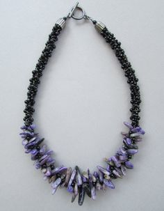 This kumihimo necklace has been made with stick Charoite, Onyx, Chinese crystal and gunmetal chain. The cones and toggle are also gunmetal, so please be aware if you have any metal sensitivities! Charoite is a beautiful bright purple stone found in Eastern Siberia.    The necklace measures approximately 20 in length.