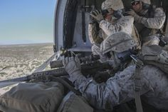 A U.S. Marine Corps Scout Sniper prepares to fire a M110 SASS rifle from inside a Black Hawk helicopter.