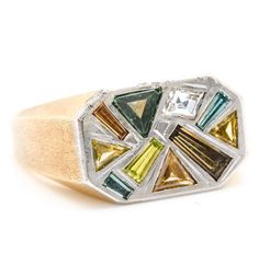 An 18K yellow and white gold signet ring with a textured, 18K yellow gold Eurostyle shank, containing 1.62 ctw of white and fancy multi-colored diamond center stones. The stones feature mixed cuts, and are flush set within a 14K white gold head with canted corners (via The Ganoksin project fb page)