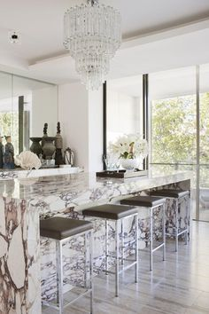 Glass chandelier + marble = drama... clever to continue counter top material down to the floor on the bar stool side!