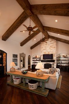 Love the stained beams, the floor to ceiling fireplace, the sofa table, and the wire baskets underneath. Such great ideas!