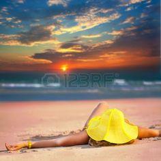 Mujer de sombrero amarillo se encuentra en la playa