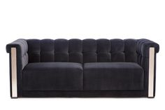 This Tufted Sofa features brass metal arm plates and maple wood legs.