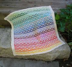 Rainbow Chain by Erika Flory. A classic chain stitch is updated here as an off-white grid that lays over the rainbow of colors that move from yellow all the way through green. Working with only one color per row keeps the pattern simple and easy to memorize. The border is knitted as the blanket is worked so the finishing is quick: just work in loose ends.