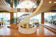 amazing foyer. look at that staircase and water fountain!