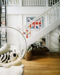 A playful bubble chair at the base of a white staircase