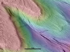A piece of Mars: Topography in color is draped over an image of a windblown cliff. The entire shape of the landscape here was formed by wind, from the large 400 m (1312 ft) tall zigzag cliff, to the small streamlined shapes in the valley. Even the deep gorge that looks like a stream channel was formed by winds, all blowing toward the upper left. (HiRISE PSP_006694_1895 NASA/JPL/Univ. of Arizona, HRSC ESA/DLR/FU Berlin)