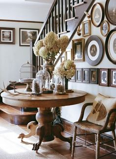A wide variety of rectangular and circular frames in an entryway and staircase.