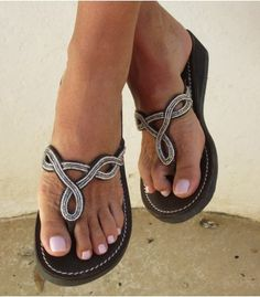 The Zanzibar leather beaded sandal features an elegant pattern of pretty silver beads on a black leather upper with a small heel.       This product is handmade in Africa    Thong Style Sandal    Genuine Dark Leather Upper (dyed & sun dried) with contrast white stitching    Small Rubber Wedge Heel (1.5 inches)    Hand-cut uppers and soles    All bead work sewn by hand