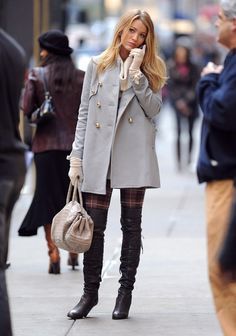 Blake Lively is wearing a grey peacoat, plaid bottoms and thigh-high black boots in Gossip Girl.