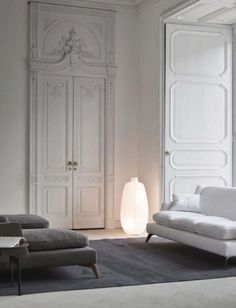 Classical apartment in white and grey tones with moldings and high doors _