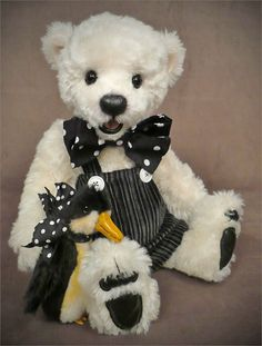 Cream colored teddy bear dressed in black pin stripped overalls and polka dot suspenders. So cute and ready for sitting in your Holiday Christmas tree.