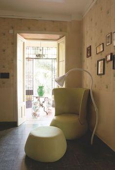 """Dans le coin lecture tapissé d'un papier peint ancien, fauteuil et repose-pieds """"Fat Sofa"""" de Patricia Urquiola, B&B Italia. Lampe """"Pipe"""" de Herzog & De Meuron, Artemide. Dans le fond, une petite table des années 1920. Posée dessus, vase """"La Bohême"""" de Philippe Starck pour Kartell."""
