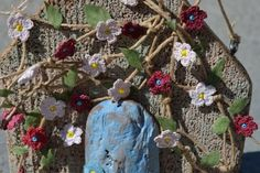 #Crochet flowers on driftwood from Flowers and Driftwood