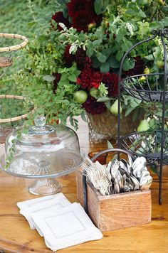 A wooden basket holding silverware for the guests is displayed with a large arrangement of pears and red dahlias.
