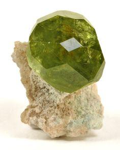 Andradite (Var: Demantoid), Ca3Fe+++2(SiO4)3, Antetezambato Demantoid-Topazolite Mine, Antetezambato, Maherivaratra Commune, Ambanja District, Diana Region, Antsiranana Province, Madagascar. Dimensions: 1.9 x 1.7 x 1.5 cm. A single glassy and gemmy, light green crystal of demantoid, measuring 1.3 cm across, is aesthetically perched on a metasomatized limestone matrix. Copyright: © Rob Lavinsky