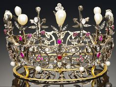 A 19th century ruby, natural pearl and diamond crown, circa 1890 The openwork circlet of scrolling foliate design set throughout with rose and old brilliant-cut diamonds, with cushion-shaped ruby highlights, culminating in alternating claw-set diamonds and pear-shaped pearl finials