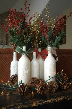 Christmas Centerpiece. Wine bottles, spray paint, spray adhesive, epson salt, puff paint, and a bunch of Christmas love (pine and berries) stuffed inside!