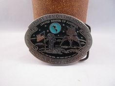 """This is a great belt buckle which commemorates the first manned moon landing in 1969.  First Men on the Moon 20 Year Commemorative 1969-1989 One small step for man, one small leap for mankind.  This pewter belt buckle is in great vintage condition. The enamel is still sharp and clear.  3.25"""" x 2.5"""" Made in USA  Great stocking stuffer, Christmas present, birthday gift, or Fathers Day gift. Great NASA gift.  Free US Shipping.  To see more vintage at The Snap Dragon's Lair - www.etsy.com/sh..."""