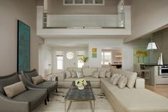 Comfortable, elegant and functional, this coastal living room features a two-story catwalk and relaxed neutral furniture. Colorful art make an eye-catching accent piece.: