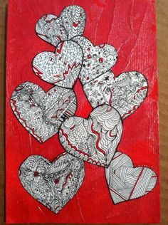 cut out zentangle hearts on a textured red background ... edges blackened to ake the stand out ... like the touches of red on each to tie in the background color ...