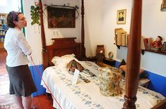 A visitor looks at Frida Kahlo's bed with her Dead Mask during a visit to the Blue House museum