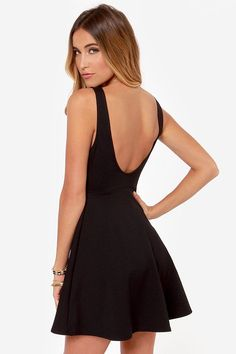 Perfectly posh black knit material forms a fitted sleeveless bodice with a rounded neckline and princess seams that moves outward to a full skater skirt