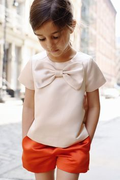 Beautiful cream bow top with orange shorts, the material is amazing on this girls outfit. Loving this kids fashion for girls, SO cute! Would be an adorable outfit for a tween too. Little Girl Outfits, Little Girl Fashion, Toddler Fashion, Fashion Children, Girls Fashion Kids, Kids Girls, Baby Girls, Outfits Niños, Kids Fashion Photography