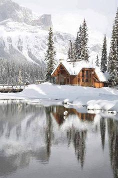 Emerald Lake Lodge in Canadian Rocky Mountain  water mirror reflection, snow, mountain peaks, cabin