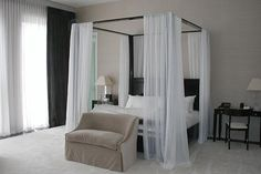 Beautiful, contemporary bedroom including a canopy bed with sheer white curtains, from Jennifer Post Design.